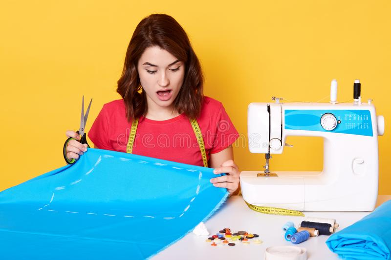 Young woman dressmaker sewing in her studio, being frustrated because she making mistake, sitting with opened mouth, holds stock photography
