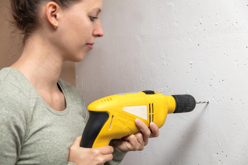Young woman drilled a hole in the wall stock images