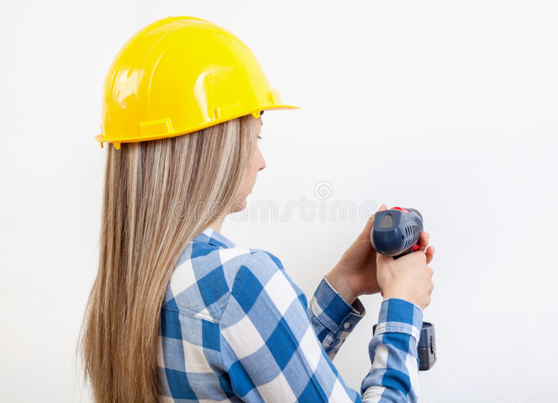 Young woman drilling a hole in the wall royalty free stock photos