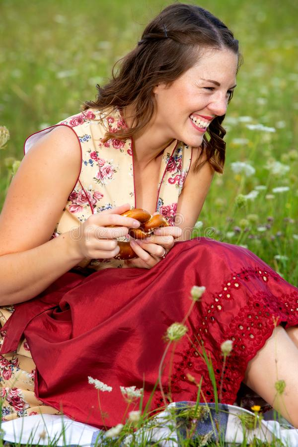 Young woman in drindl sitting in a meadow and laughing stock photos