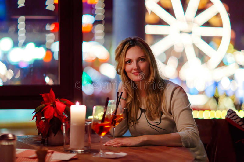 Young woman drining cocktail in restaurant stock images