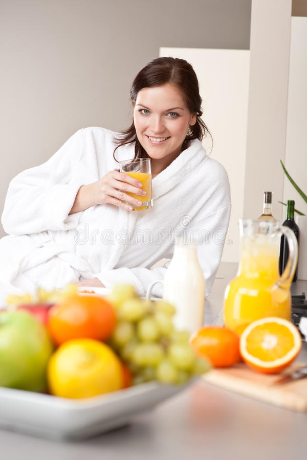 Young woman drink orange juice in kitchen royalty free stock image