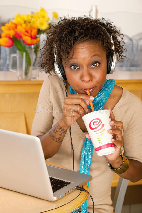 Download Young Woman Drinking Beverage And Using Laptop Stock Image - Image: 14787877
