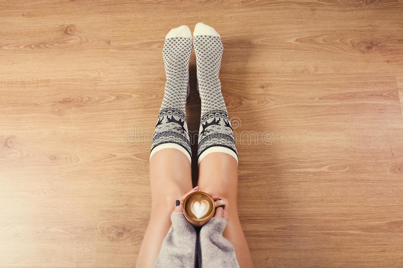 Young woman drinking cappuccino coffee and sitting on the wooden floor. Close up of female hands holding cup of coffee, sitting on royalty free stock photo