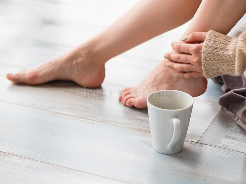 Young woman drinking cappuccino coffee and sitting on the wooden floor. Close up of female legs and cup of coffee stock photo