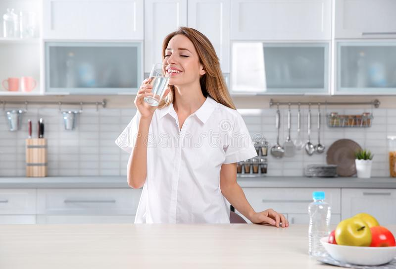 Young woman drinking clean water from glass stock image