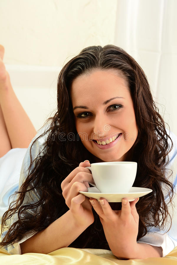 Young woman drinking coffee in bed royalty free stock photos