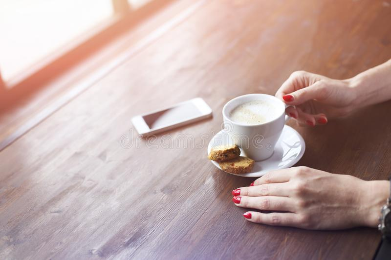 Woman drinking coffee in cafe near window top view royalty free stock photo