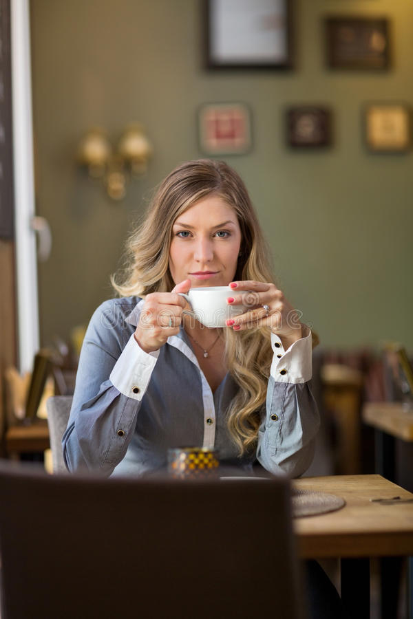 Young Woman Drinking Coffee At Cafe royalty free stock image