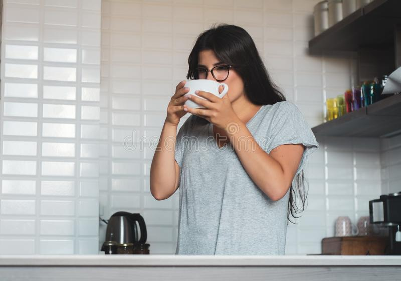 Young woman drinking coffee at home stock photography