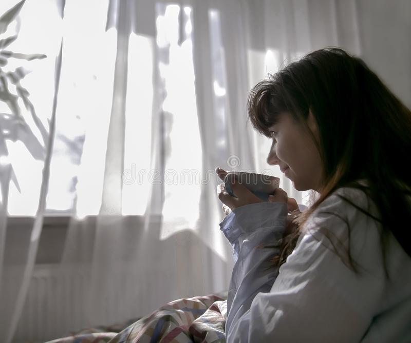 Young woman drinking coffee while sitting in bed, against the window. Young brunette woman drinking coffee while sitting in bed, against the window royalty free stock photos