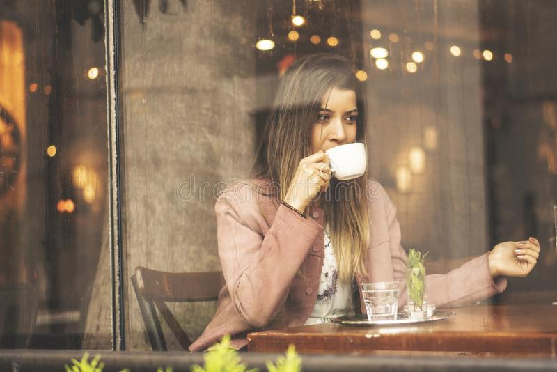 Young woman drinking coffee sitting indoor in urban cafe. Pretty cute girl and holding cup of coffee stock photography