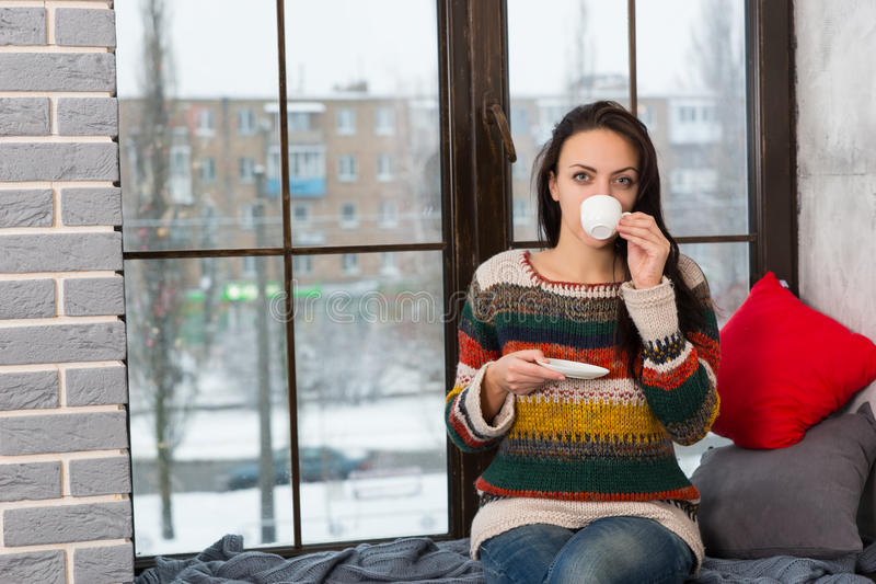 Young woman drinking coffee while sitting on windowsill. With pillows and blanket in the living room royalty free stock image