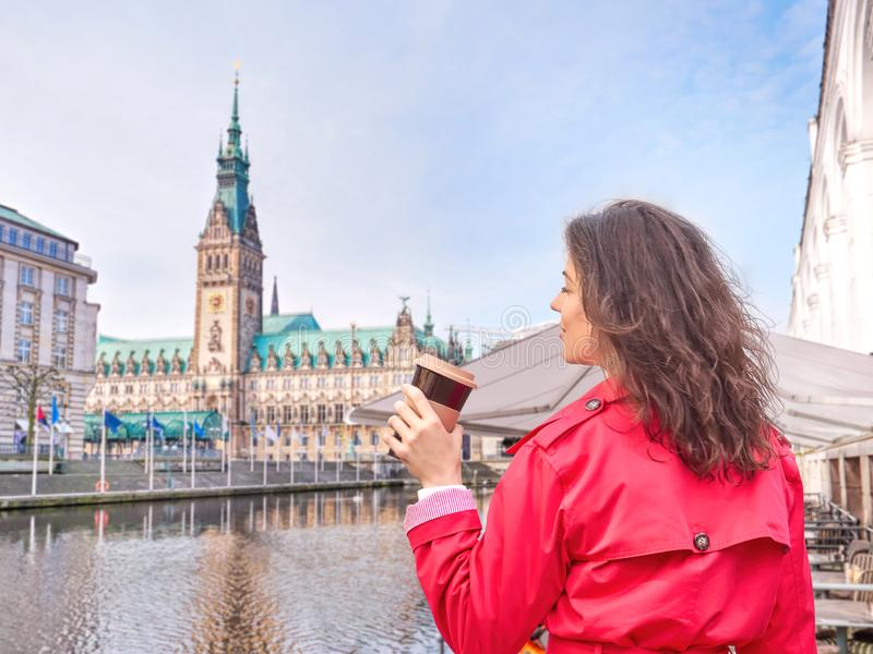 Young woman drinking coffee and walking outdoor in Hamburg city hall square, Germany. stock images