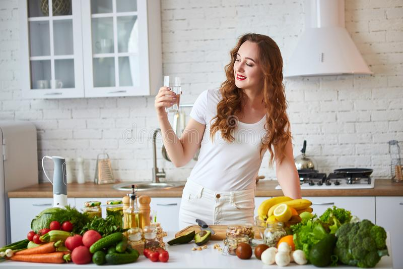Young woman drinking fresh water from glass in the kitchen. Healthy Lifestyle and Eating. Health, Beauty, Diet Concept. Young woman drinking fresh water from royalty free stock image