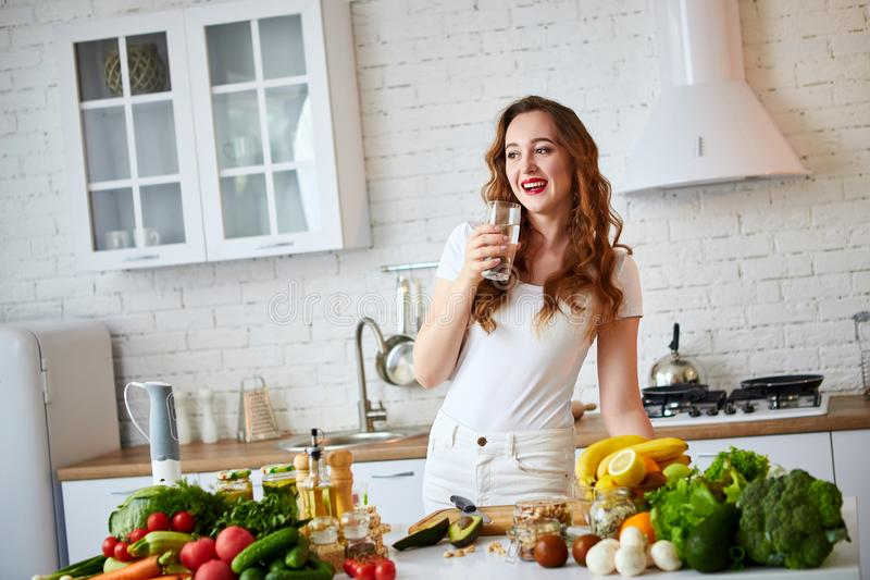 Young woman drinking fresh water from glass in the kitchen. Healthy Lifestyle and Eating. Health, Beauty, Diet Concept. Young woman drinking fresh water from stock image