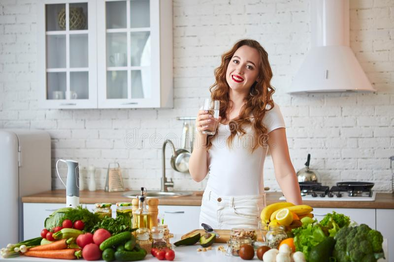 Young woman drinking fresh water from glass in the kitchen. Healthy Lifestyle and Eating. Health, Beauty, Diet Concept. Young woman drinking fresh water from stock images