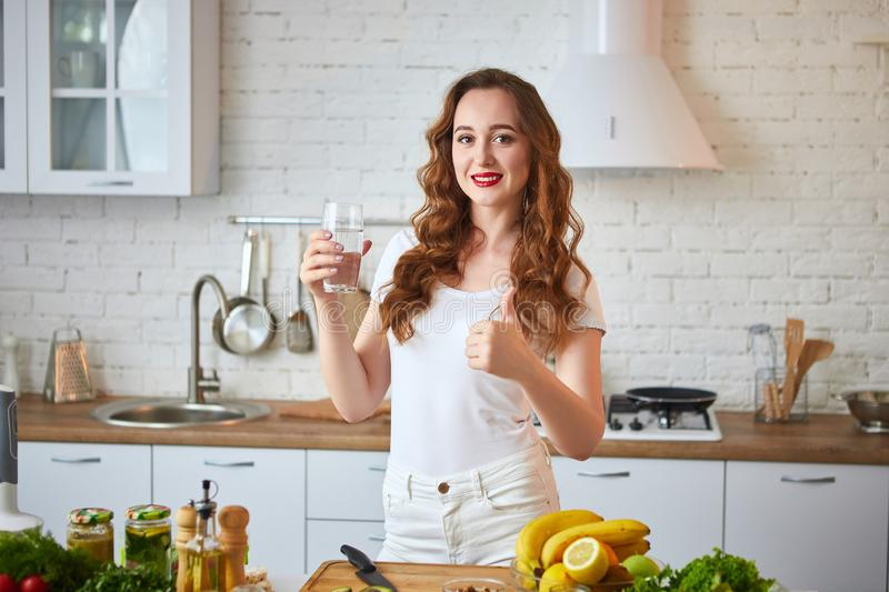 Young woman drinking fresh water from glass in the kitchen. Healthy Lifestyle and Eating. Health, Beauty, Diet Concept. Young woman drinking fresh water from stock photography