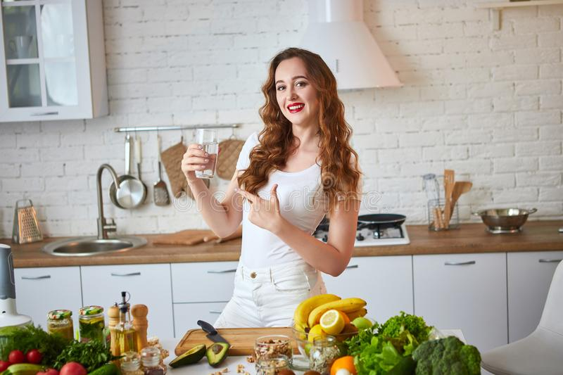 Young woman drinking fresh water from glass in the kitchen. Healthy Lifestyle and Eating. Health, Beauty, Diet Concept. Young woman drinking fresh water from royalty free stock photos