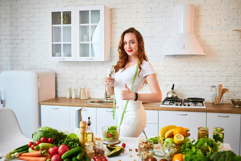 Young woman drinking fresh water from glass and showing thumbs up in the kitchen. Healthy Lifestyle and Eating. Health, Beauty,. Young woman drinking fresh water stock photos