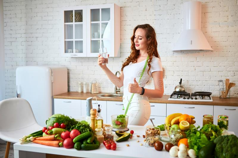 Young woman drinking fresh water from glass and showing thumbs up in the kitchen. Healthy Lifestyle and Eating. Health, Beauty,. Young woman drinking fresh water royalty free stock images