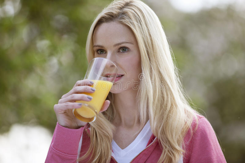 A young woman drinking a glass of orange juice outside royalty free stock photo