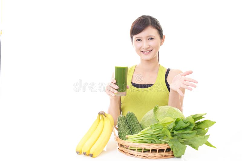 Woman with a glass of vegetable juice. Young woman drinking a glass of vegetable juice stock photography