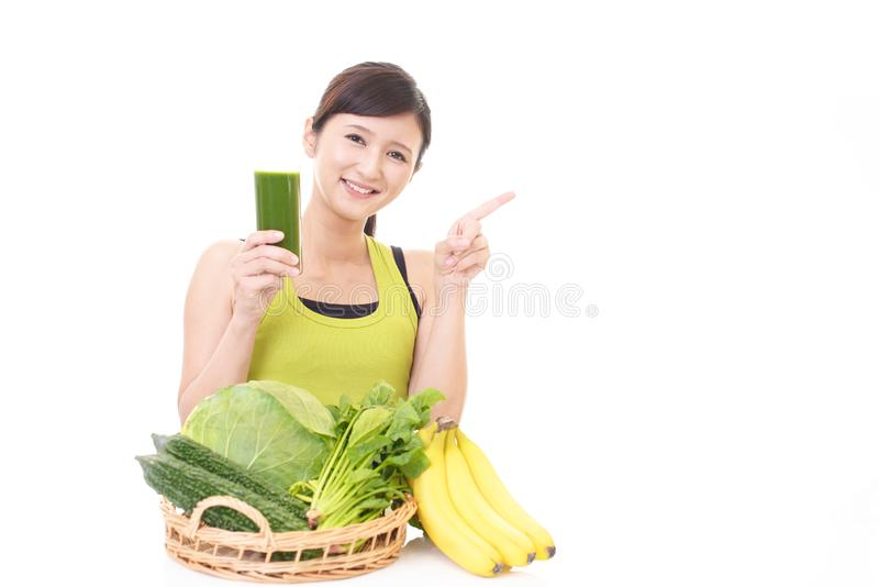 Woman with a glass of vegetable juice. Young woman drinking a glass of vegetable juice royalty free stock images
