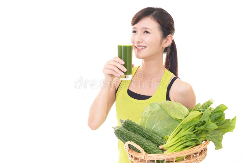 Woman with a glass of vegetable juice. Young woman drinking a glass of vegetable juice stock image