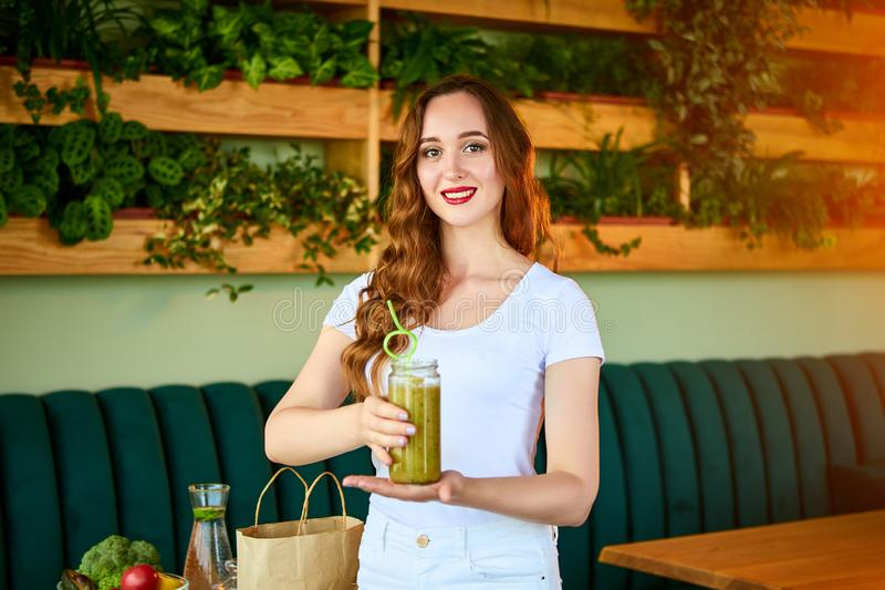 Young woman drinking green smoothie on the kitchen table with fruits and vegetables. Healthy eating concept. Vegan meal and detox stock image