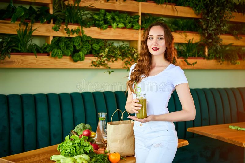 Young woman drinking green smoothie on the kitchen table with fruits and vegetables. Healthy eating concept. Vegan meal and detox stock photography