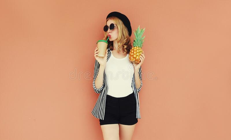 young woman drinking juice holding pineapple wearing a striped black white shirt, sunglasses, hat stock image
