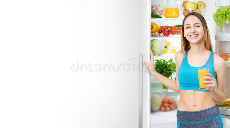 Young woman drinking juice and staying near the fridge full of health food. stock image