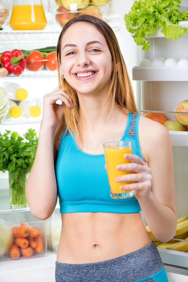 Young woman drinking juice and staying near the fridge full of health food. Fitness and healthy lifestyle concept stock photo