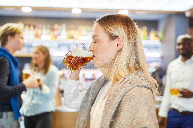 Young woman drinking with pleasure a glass of beer in the pub royalty free stock image