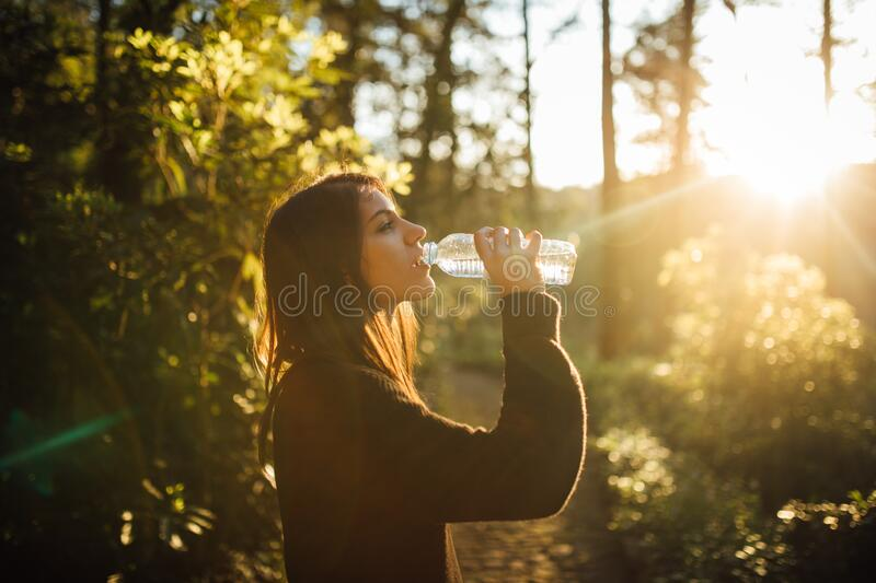 Young woman drinking water from bottle in nature.Bottled water.Hydration.Water intake for healthy body and skin.Natural mineral royalty free stock image