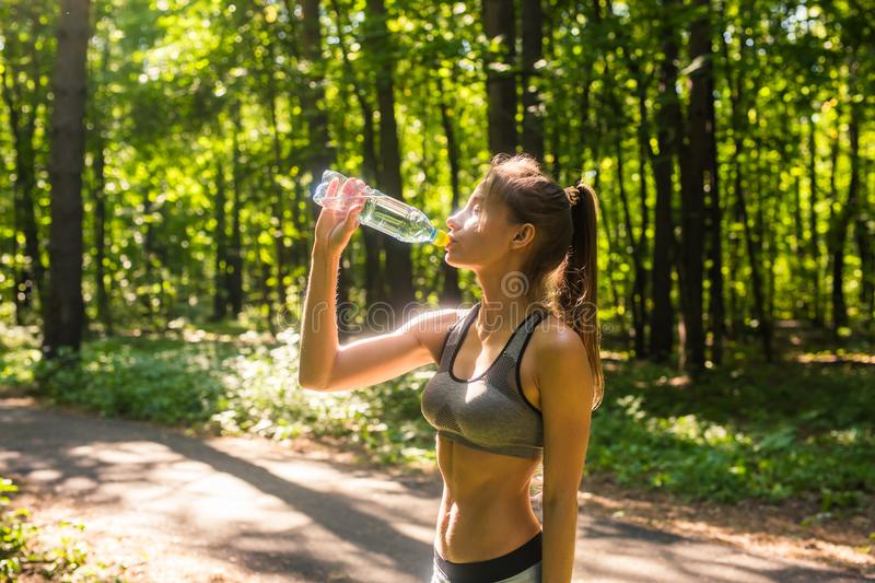 Young woman drinking water after jogging outdoors.  royalty free stock photography