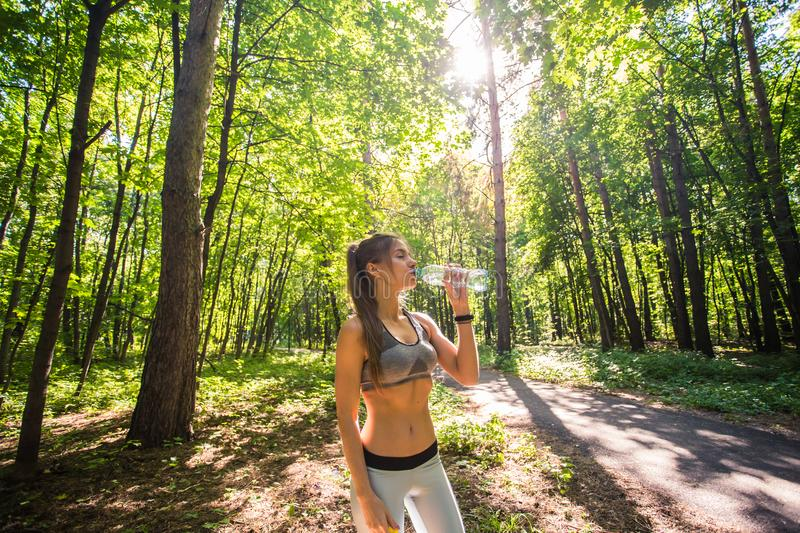 Young woman drinking water after running outdoors.  royalty free stock photos