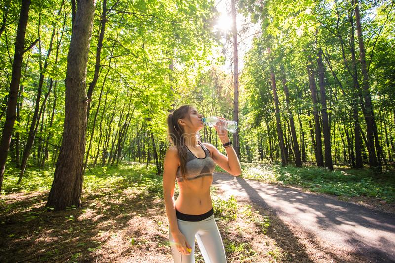 Young woman drinking water after running outdoors.  stock image