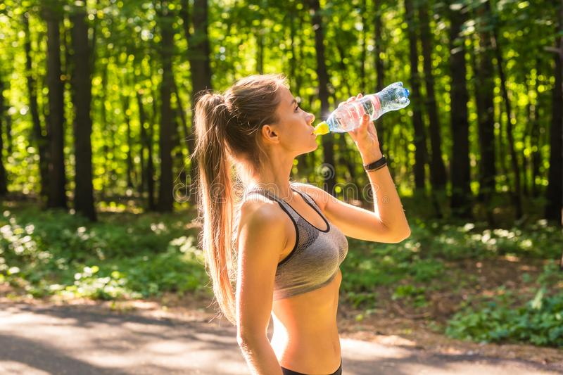 Young woman drinking water after running outdoors.  royalty free stock image
