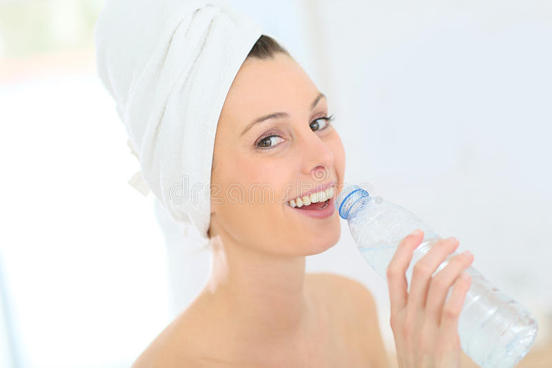 Young woman drinking water after showering stock photo