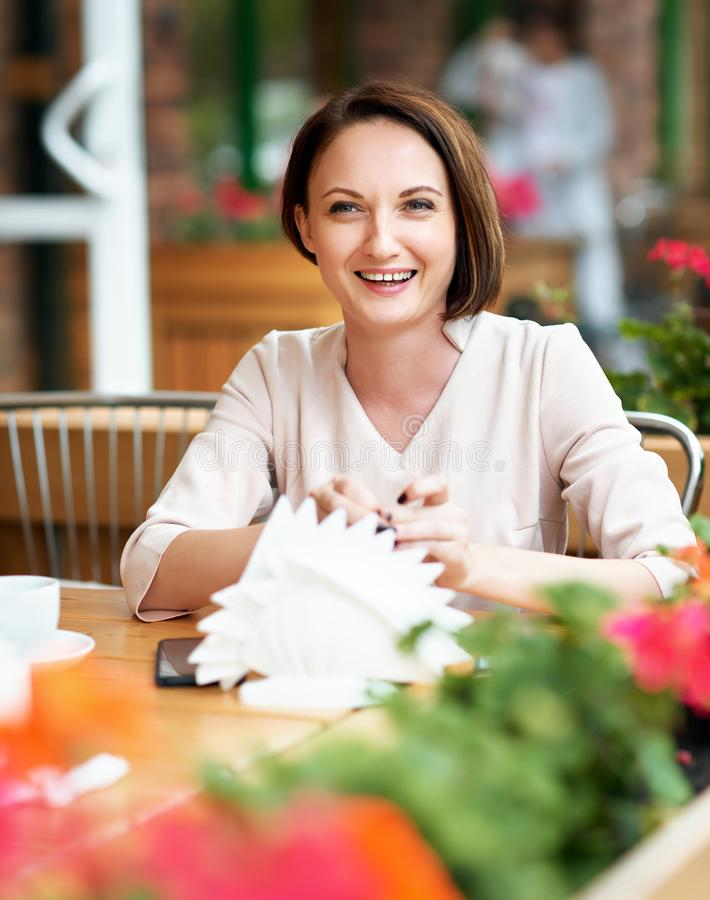 Young woman drinks coffee in cafeteria stock images