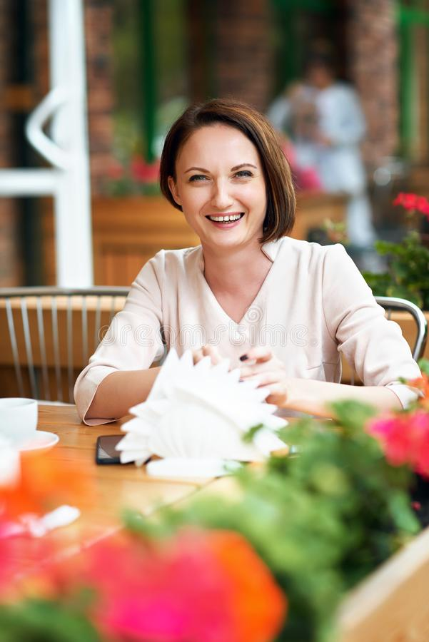 Young woman drinks coffee in cafeteria stock photography