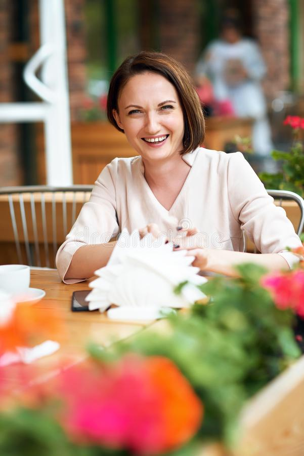 Young woman drinks coffee in cafeteria stock image