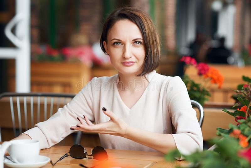 Young woman drinks coffee in cafeteria and posing with sunglasses stock photos