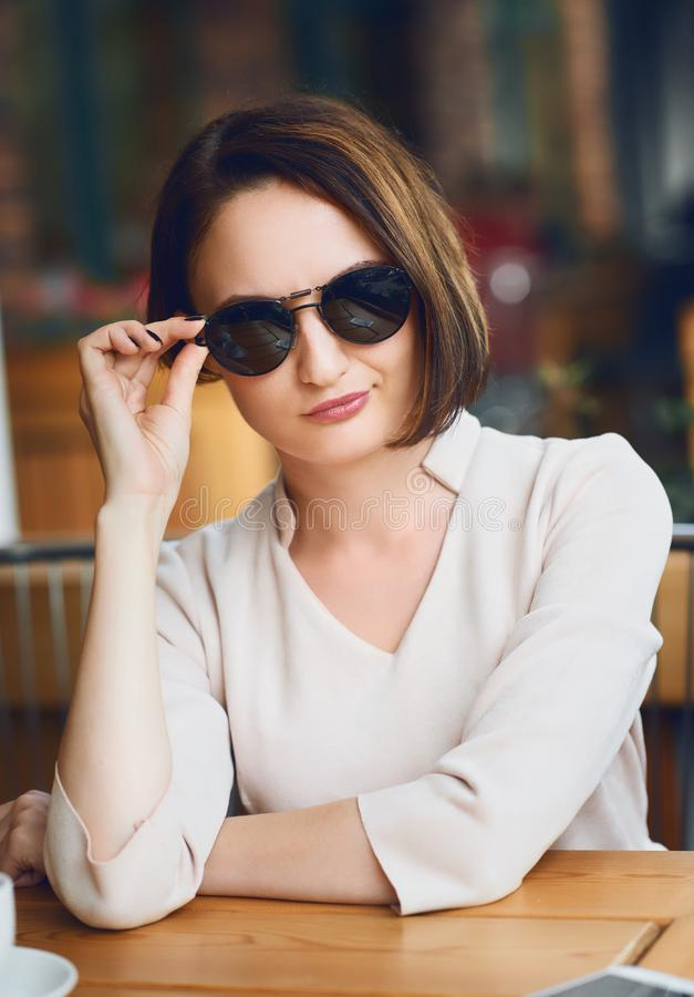 Young woman drinks coffee in cafeteria and posing with sunglasses royalty free stock photo