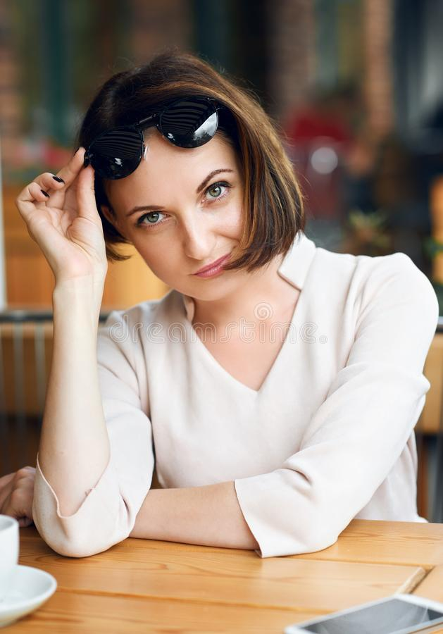 Young woman drinks coffee in cafeteria and posing with sunglasses royalty free stock image