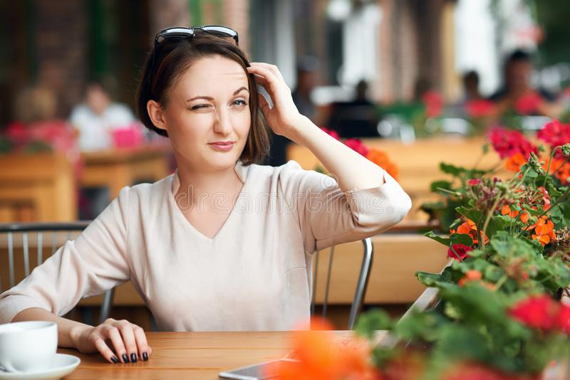 Young woman drinks coffee in cafeteria and posing with sunglasses royalty free stock photography