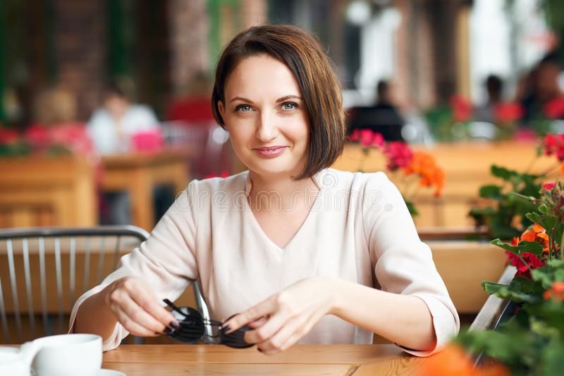 Young woman drinks coffee in cafeteria and posing with sunglasses stock photography