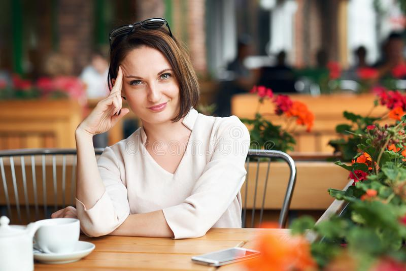Young woman drinks coffee in cafeteria and posing with sunglasses stock image